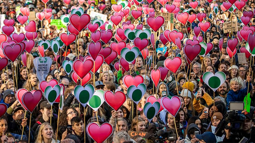 protesters march in the street holding cut outs of hearts