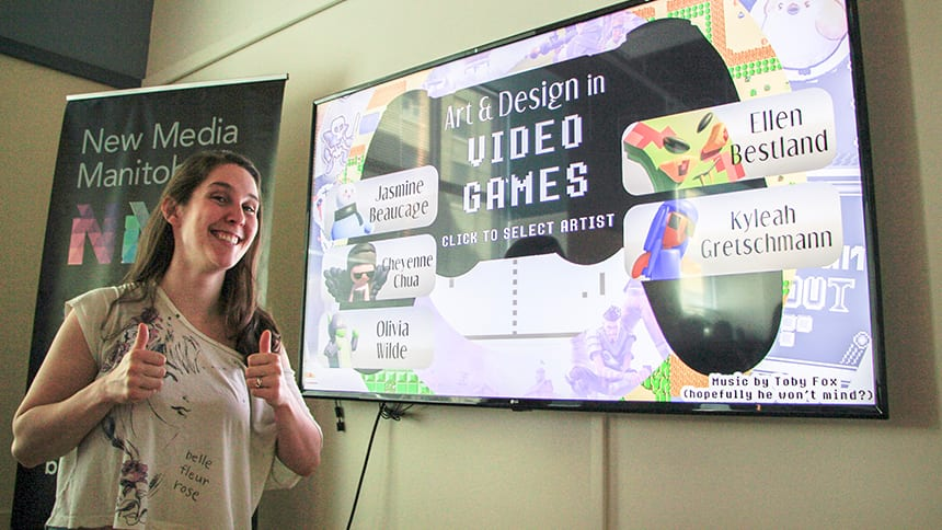 A woman gives the thumbs up sign in front of a screen about video games