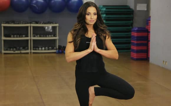 Trish Stratus demonstrates tree pose, one of three yoga moves you should do every day.