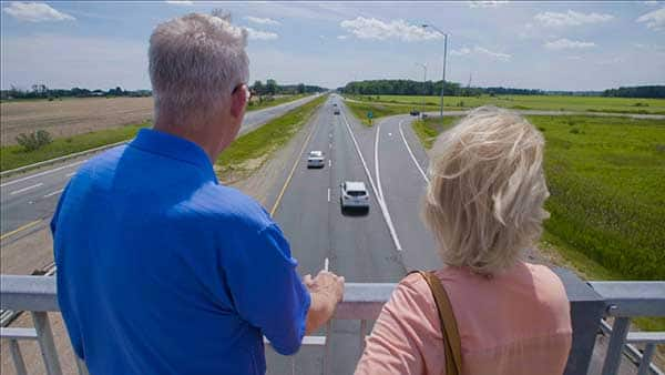 Couple standing on bridge over a highway