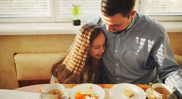 Father and daughter enjoy breakfast together.