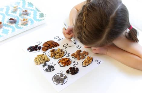 A little girl using a marker to add up the snacks by 10s