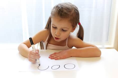 A little girl drawing circles on a piece of paper