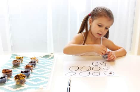 A little girl starting to sort the snacks into the circles drawn on paper