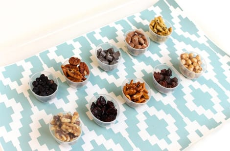 10 different kinds of snacks separated into bowls and ready to be mixed and counted for your 100 Day snack jars