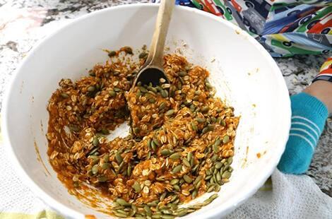 Pumpkin mixture with pumpkin seeds mixed with wooden spoon.