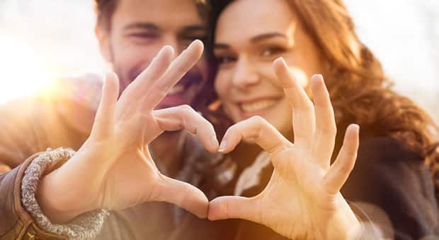 Couple makes heart hands