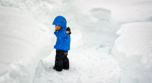 A little boy all bundled up in the snow