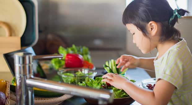 Little girl helps out with dinner