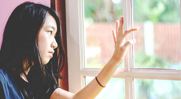 Young girl stares out the window