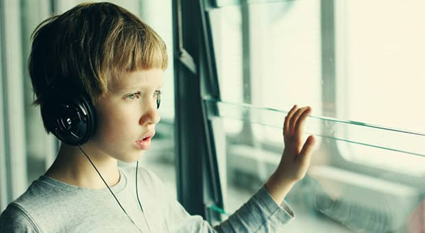 Boy with headphones looks out the window.
