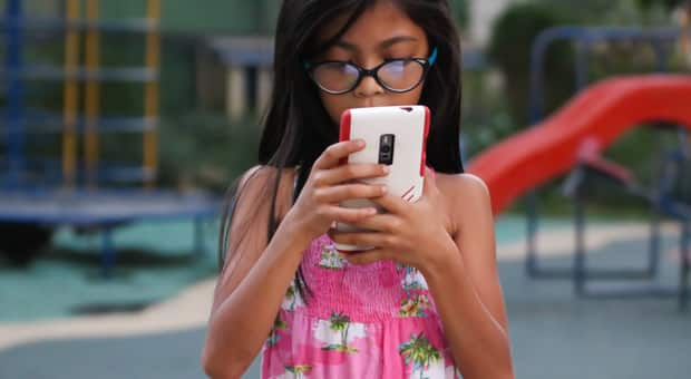 A little girl looking at her phone