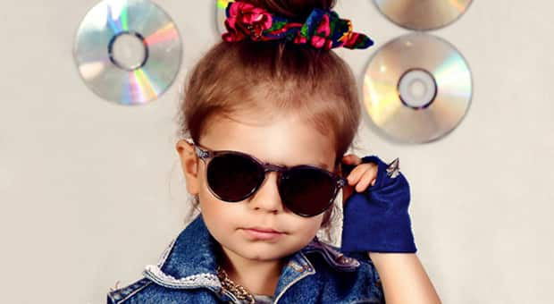 Little girl in a denim vest and sunglasses with a scrunchie in her hair