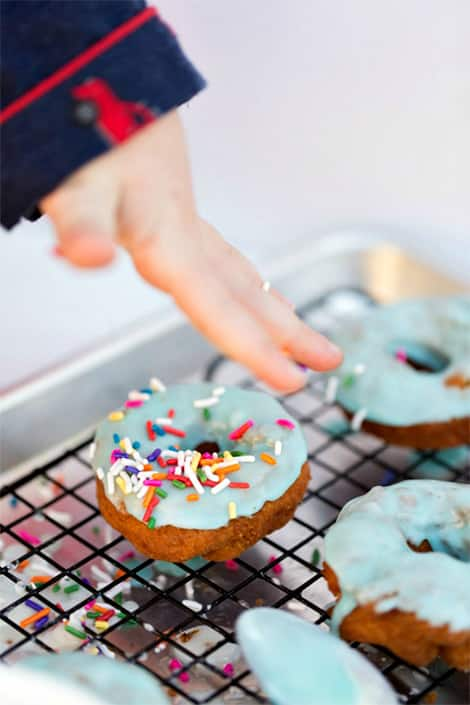 Child adds rainbow sprinkles to doughnuts.