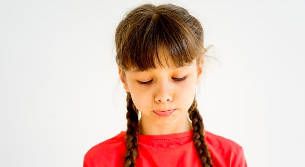 A young girl looks sad.