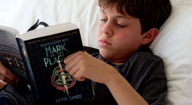School age boy lays on bed reading novel.