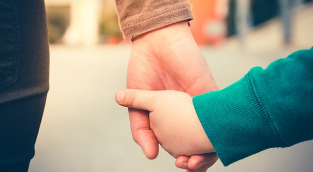 A child holding their mother's hand