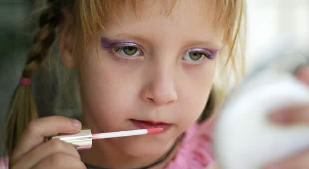 Young girl applies makeup