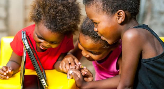 Three young girls gathered around a tablet