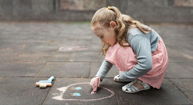 little girl plays with chalk outside on pavement
