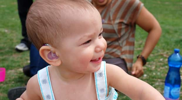 A little girl with a purple hearing aid