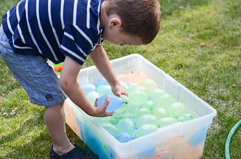 Boy reaches for water balloons in bucket.