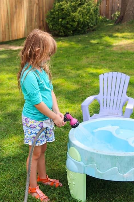 Little girl adds water to pool.