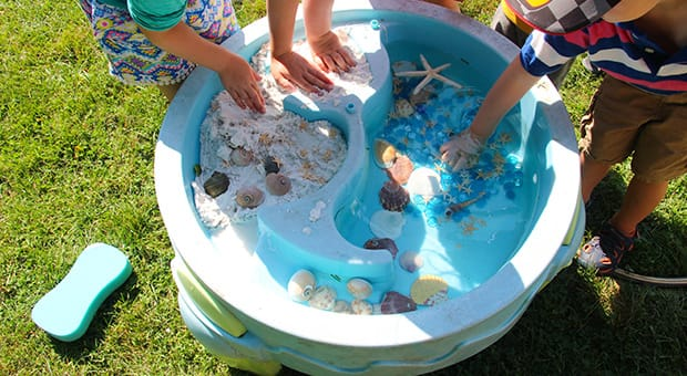 Little people play with beachwater table set-up.