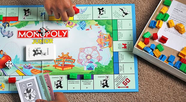 Player reaches across the monopoly board game.