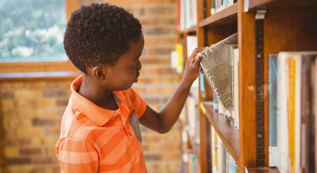 Boy taking out a book from a bookshelf.