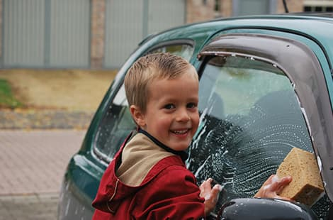 Young boy washes car.