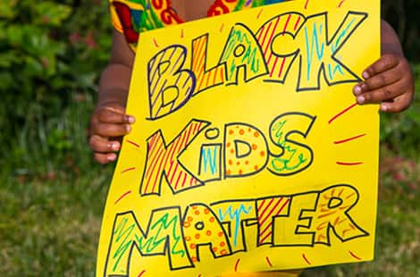 Young girl holds up Black Kids Matter poster