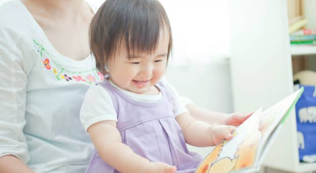 Child reading with her mother and smiling