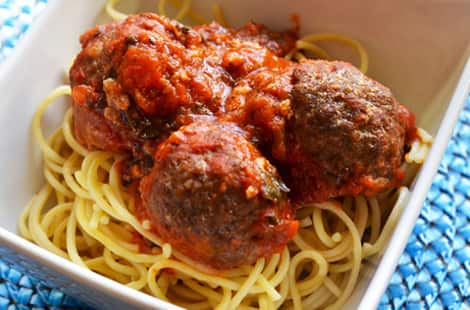 Three meatballs on a bed of spaghetti in a bowl