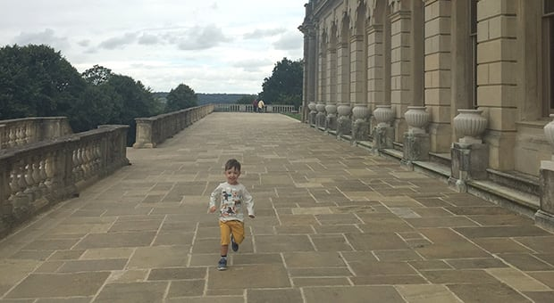 Child running beside a historic building in Britain