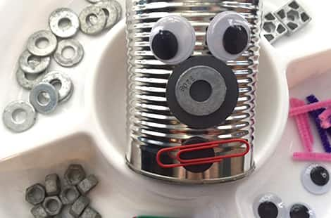 Tin can with a face made from googly eyes, washers and paperclips.