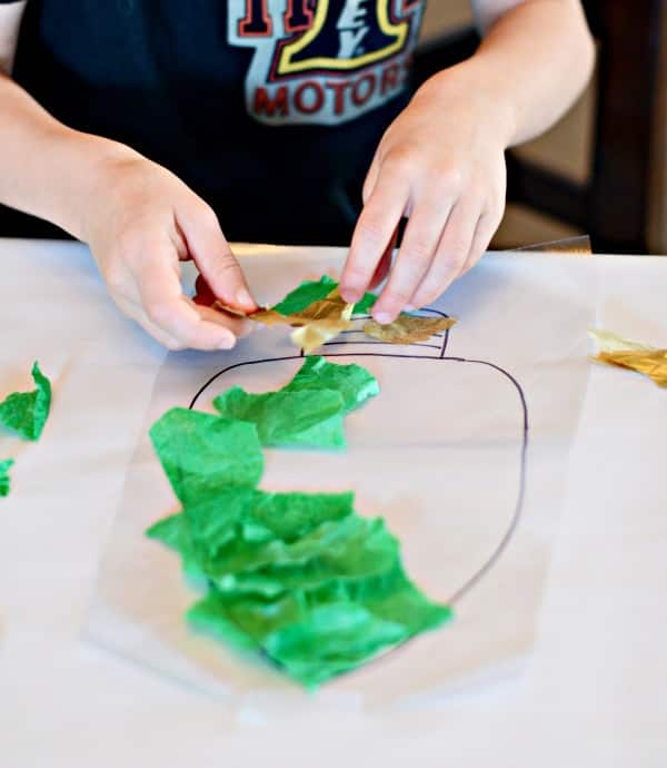 A kid tears green tissue paper into squares.