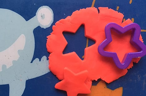 Star-shaped cookie cutters is used on play dough.