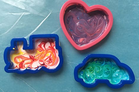Fun-shaped cookie cutters filled with glue and food colouring on parchment paper.