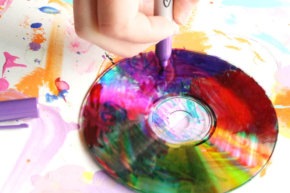 A child colours a CD with bright colours.