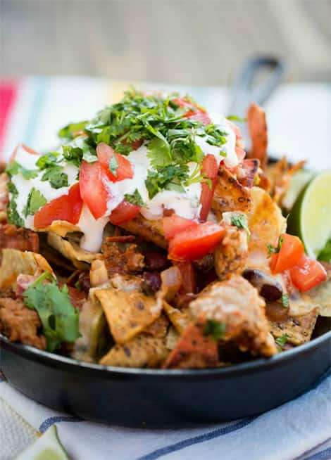 All-dressed nacho chips with chili, sour cream, sliced tomatoes, sour cream, with cilantro on top!