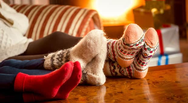 Three pairs of feet wearing woolly socks relaxing on the coffee table.