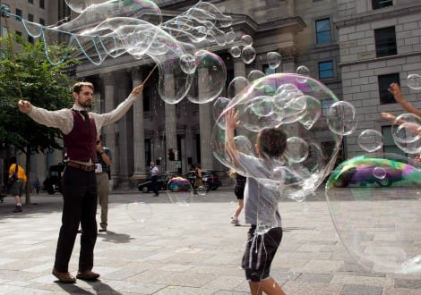 A street-performer creating dozens of giant bubbles in Old Montreal as a child plays amongst them
