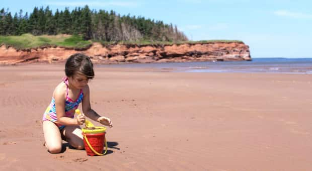 Little girl playing in the red sand of Cabot Beach, Prince Edward Island