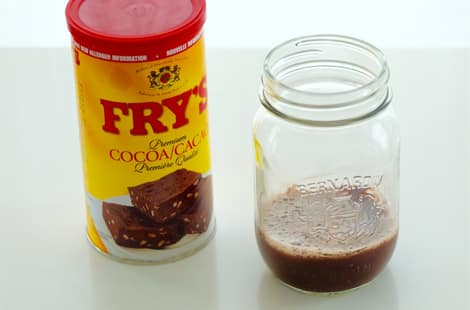 A container of cocoa beside a mason jar of DIY chocolate shampoo