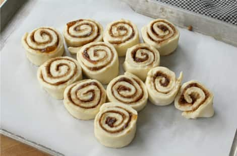 12 cinnamon buns laid out in the shape of a Christmas tree on a baking sheet, ready to be put in the oven