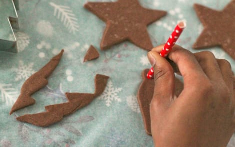 Using a straw to poke holes at the top of the ornaments