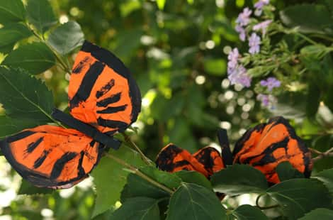 Two completed coffee filter monarch butterflies in the garden