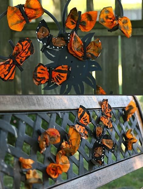 Completed coffee filter monarch butterflies clipped to a bench, with some clipped to a plant holder