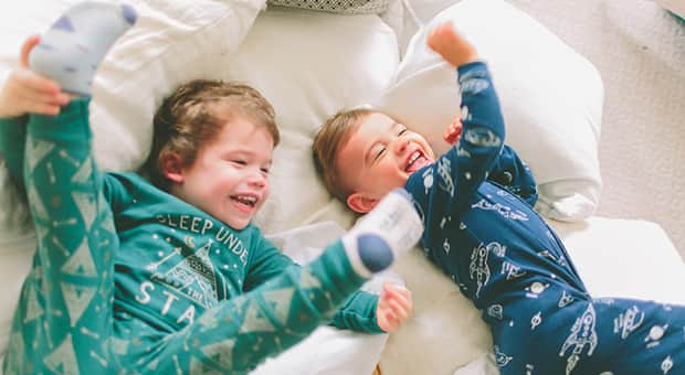 Two boys laughing and playing together on a bed
